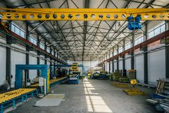 Insulation sandwich panel production line. Machine tools, roller conveyor and gantry crane in workshop.  royalty free stock photos