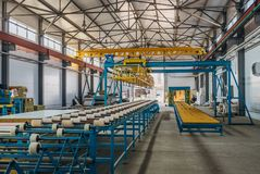 Insulation sandwich panel production line. Machine tools, roller conveyor and gantry crane in workshop.  stock photos