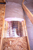 Insulation Stages of Attic. Insulation of attic with fiberglass cold barrier and reflective heat barrier between the attic joists, work is ongoing royalty free stock image