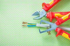 Insulation strippers nippers electric wires on green background Royalty Free Stock Photos
