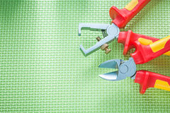Insulation strippers sharp nippers on green surface electricity Royalty Free Stock Images