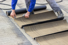 Insulation worker cutting insulation bitumen material rolls Stock Image