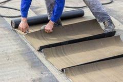 Insulation worker cutting insulation bitumen material rolls Stock Image