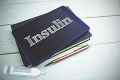 Insulin against view of a book and tablet lying on desk Stock Photography