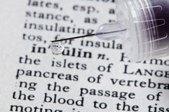 Insulin drips from syringe onto the word insulin. Drop of insulin with insulin reflection stock image