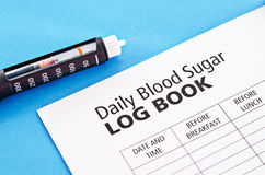Insulin injection pen. Insulin injection pen with daily blood Log Book on blue background Stock Photo