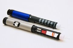 Insulin pen. Two metal insulin pen on a white background stock photos