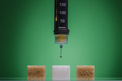 Insulin pen and sugar cubes. Against green background Stock Photos