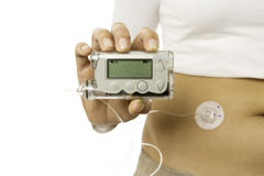 Insulin pump. Closeup of a hand holding an insuline pump isolated on a white background royalty free stock photo