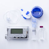 Insulin pump set background. Top view of an insulin pump set background consisting of: an insulin pump, insertion system of the infusion set, a reservoir of an Royalty Free Stock Image