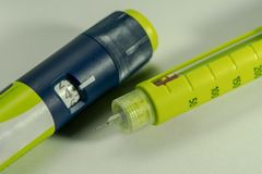 Insulin syringe or injector of pen model with dose setting knob and scale window and a one time throw away needle in bright yellow. Color, on white background stock photos