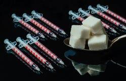 Insulinabhängigkeit: Spritzen und Zucker stockbilder