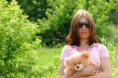 Insult. The girl in a sun-protection point on a summer meadow with a bear cub Royalty Free Stock Photography