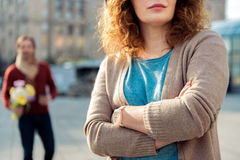 Insulted lady waiting for her boyfriend on street. Offended women is standing outdoors with crossed hands. Man is walking to her with bouquet of flowers on Royalty Free Stock Images