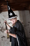 Insulted Young Wizard with Scepter. Menacing teenager dressed as wizard with tall hat and scepter royalty free stock photography