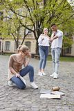 Two insulting students abusing their fellow student. Insulting students. Two insulting students abusing their fellow student dropping her things on the ground Stock Image