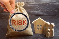 Μια τσάντα με τα χρήματα και τον κίνδυνο λέξης και ένα ξύλινο σπίτι Ιδιοκτησία αγοράς με την πίστωση Η έννοια του οικονομικού κιν στοκ εικόνες