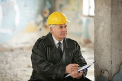 Insurance adjuster in devastated room of abandoned building royalty free stock image
