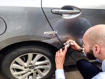 Insurance adjuster examining damage to car exterior Royalty Free Stock Images