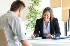 Insurance agent and customer calculating budget stock photo