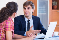 Insurance agent and customer discussing agreement terms Stock Photo