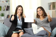 Insurance agent and disabled client with thumbs up. Happy insurance agent and disabled client showing contract with thumbs up at home stock images