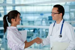Insurance agent with a doctor handshaking Stock Images