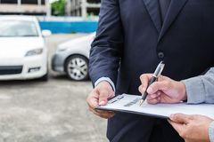 Insurance Agent examine Damaged Car and customer filing signatur. E on Report Claim Form process after accident, Traffic Accident and insurance concept Royalty Free Stock Image
