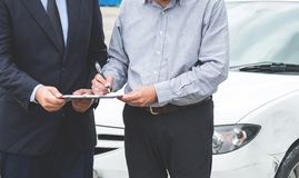 Insurance Agent examine Damaged Car and customer filing signatur. E on Report Claim Form process after accident, Traffic Accident and insurance concept Stock Image