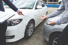 Insurance Agent examine Damaged Car and filing Report Claim Form. After accident, Traffic Accident and insurance concept Royalty Free Stock Image