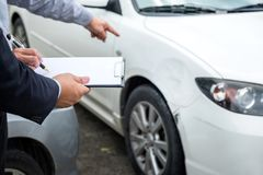 Insurance Agent examine Damaged Car and filing Report Claim Form. After accident, Traffic Accident and insurance concept Stock Images