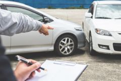 Insurance Agent examine Damaged Car and filing Report Claim Form. After accident, Traffic Accident and insurance concept Royalty Free Stock Photo
