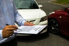 The insurance agent examining car after accident on the road. In stock photography