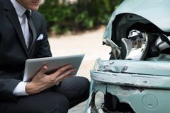 Insurance agent examining car after accident Stock Photography