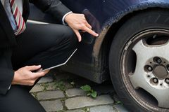 Insurance agent examining car damaged. Insurance Agent Holding Digital Tablet Examining Car Damaged After Accident Stock Image