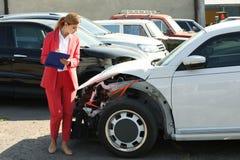 Insurance agent filling claim form near broken car. Outdoors stock photos