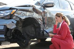 Insurance agent filling claim form near broken car. Outdoors stock image