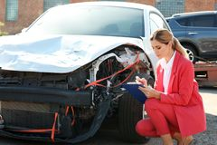 Insurance agent filling claim form near broken car. Outdoors stock photography