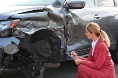 Insurance agent filling claim form near broken car. Outdoors stock images
