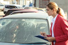 Insurance agent filling claim form near broken car. Outdoors royalty free stock image