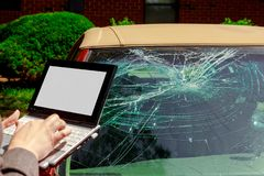 Insurance agent filling Insurance claim form on laptop after car accident, windshield crash. Insurance agent filling Insurance claim form on laptop after royalty free stock photos
