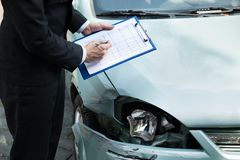 Insurance agent inspecting car after accident. Midsection of writing on clipboard while insurance agent inspecting car after accident Stock Photography