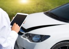 Insurance agent inspecting damaged car with insurance claim form on digital tablet royalty free stock photo