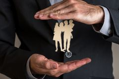 Insurance agent making protecting gesture around a paper cut sil Royalty Free Stock Photography