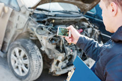 Insurance agent photographing car damage for claim form Royalty Free Stock Photography
