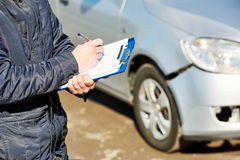 Insurance agent recording car damage on claim form Stock Images