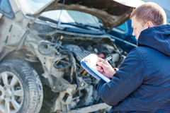 Insurance agent recording car damage on claim form Royalty Free Stock Images