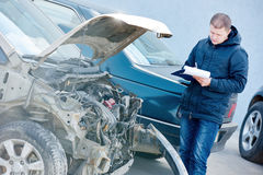 Insurance agent recording car damage on claim form Stock Photography