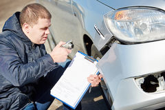 Insurance agent recording car damage on claim form. Insurance agent recording damage after car crash during inspecting damaged automobile on claim form Stock Photography