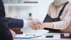 Insurance agent shaking hand with woman in arm sling, psychological support. Stock footage stock video